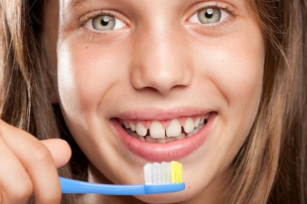 Dziewczyna szczotkuje jej zęby na szarym tle