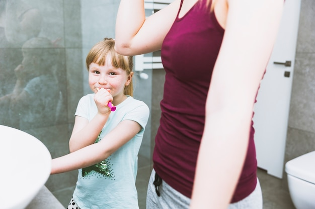 Dziewczyna szczotkuje zęby blisko matki