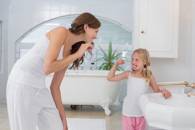 Dziewczyna szczotkuje zęby gdy patrzeje jej matki