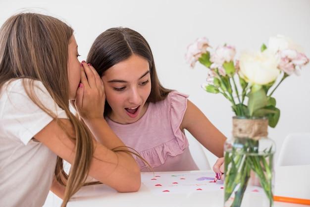 Dziewczyna szepcząca coś do siostry