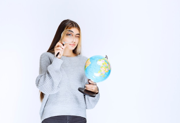 Dziewczyna szuka lokalizacji na całym świecie za pomocą lupy.