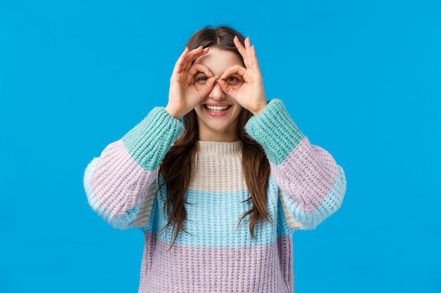 Dziewczyna szuka najlepszych rabatów na zakupy, dobrych ofert. ładna, charyzmatyczna kobieta w zimowym swetrze, trzymająca kółka dobre znaki na oczach, jakby robiła okulary z palców, uśmiecha się radośnie