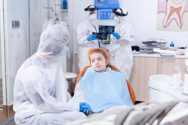 Dziewczyna szuka zamyślona matka siedzi na fotelu dentystycznym w kombinezonie z powodu wybuchu koronawirusa. stomatolog podczas covid19 w kombinezonie ppe, wykonujący zabieg zębów dziecka siedzącego na krześle.
