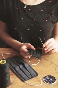 Dziewczyna szyje maski medyczne na drewnianym stole