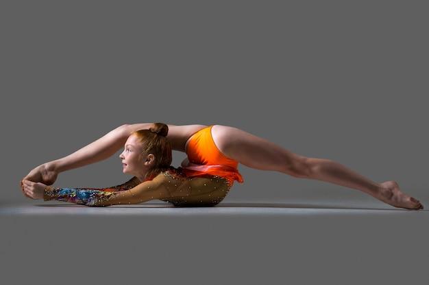 Dziewczyna tancerz robi backbend ćwiczenia akrobatyczne