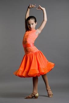 Dziewczyna tancerza tańca towarzyskiego pozy na szarym tle