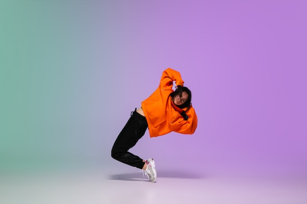 Dziewczyna tańczy hip-hop w stylowe ubrania na gradientowym tle w sali tanecznej w świetle neonu.
