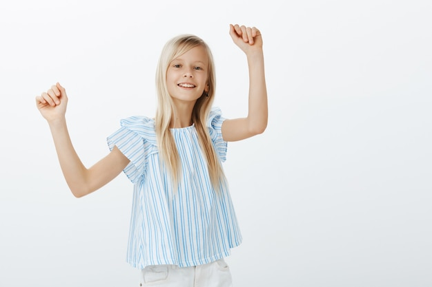 Dziewczyna tańczy na imprezie przyjaciół, dobra zabawa. kryty portret pozytywnej, wesołej, jasnej dziewczynki o jasnych włosach, podnoszącej ręce i wykonującej ruchy taneczne z radosnym uśmiechem