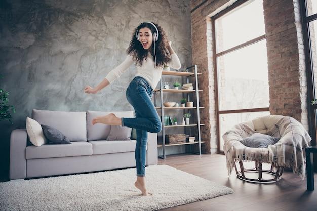 Dziewczyna tańczy słuchając muzyki, bawiąc się w nowoczesny loft industrialny styl wnętrza salonu