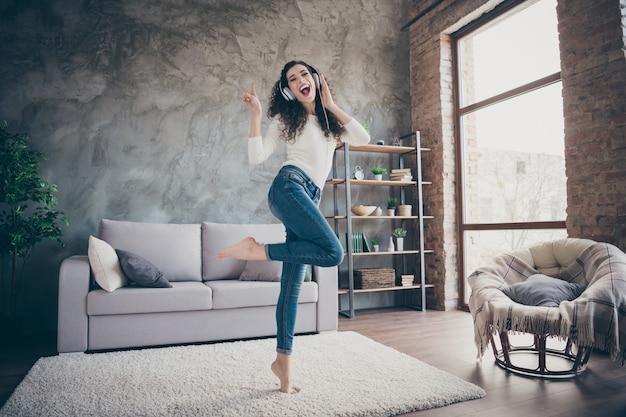 Dziewczyna tańczy słuchając muzyki, dobrze się bawiąc pokazując v-znak nowoczesny loft industrialny styl wnętrza salonu