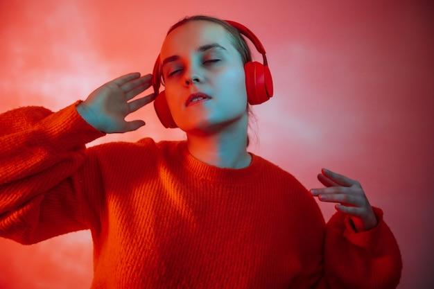 Dziewczyna tańczy w jasnym, kolorowym oświetleniu i słucha muzyki przez słuchawki