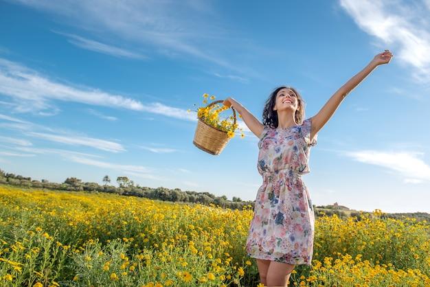 Dziewczyna tańczy wśród kwiatów w słoneczny dzień