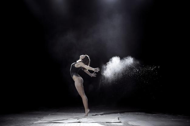 Dziewczyna tańczy z mąki na czarno