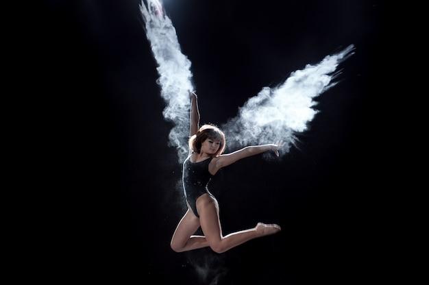 Dziewczyna tańczy z mąki na czarnym tle na scenie