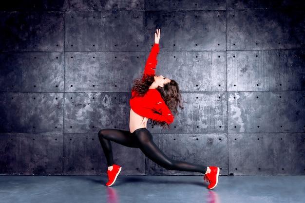 Dziewczyna taniec przed miejską ścianą.