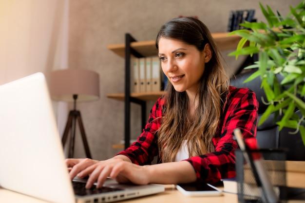 Dziewczyna telepracownika pracuje w domu z laptopem