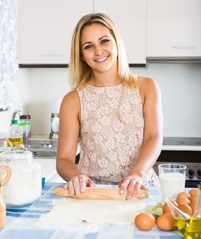 Dziewczyna toczenia ciasta na stole w kuchni