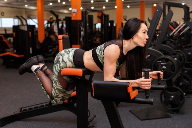 Dziewczyna trenuje na symulatorze w siłowni