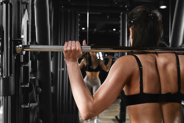 Dziewczyna trenuje nogi na siłowni ze sztangą, pozując przed lustrem