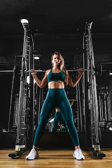 Dziewczyna trenuje nogi na siłowni ze sztangą sportowy styl życia, dbanie o kondycję, motywacja do ćwiczeń