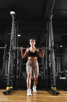 Dziewczyna trenuje nogi na siłowni ze sztangą sportowy styl życia, motywacja do ćwiczeń. ciemny