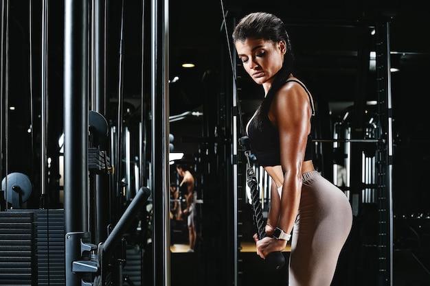 Dziewczyna trenuje ręce na siłowni na symulatorze, wykonuje rozłożone ćwiczenia rękami