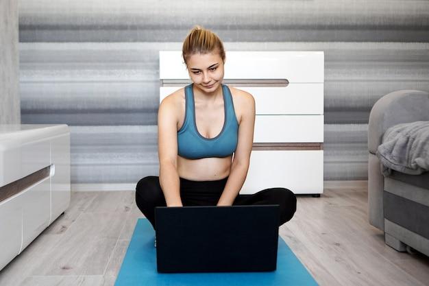 Dziewczyna trenuje w domu i ogląda filmy na laptopie przed rozpoczęciem