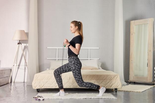 Dziewczyna trenuje w domu i robi ćwiczenia. kobieta korzystająca z kwarantanny do ćwiczeń w domu.