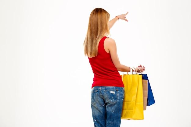 Dziewczyna trwanie kamera z zakupami nad biel ścianą z powrotem