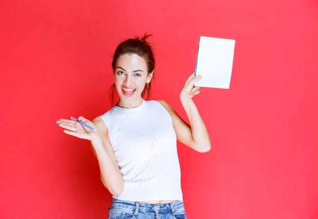 Dziewczyna trzyma arkusz egzaminacyjny i wskazuje na niego.
