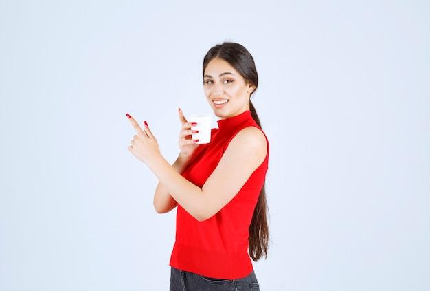 Dziewczyna trzyma białą filiżankę kawy i wskazując na nią.