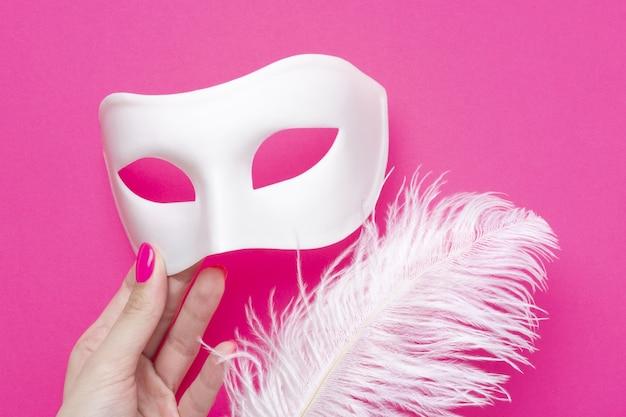 Dziewczyna trzyma białą karnawałową maskę i puszyste pióro na różowym tle fuksji