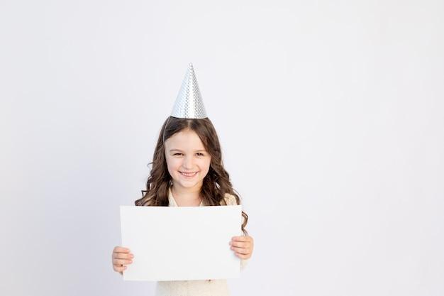 Dziewczyna trzyma białą kartkę. śliczna mała dziewczynka z białą kartką papieru na na białym tle. miejsce na tekst. mała dziewczynka trzyma pusty kawałek pape, koncepcja sprzedaży.