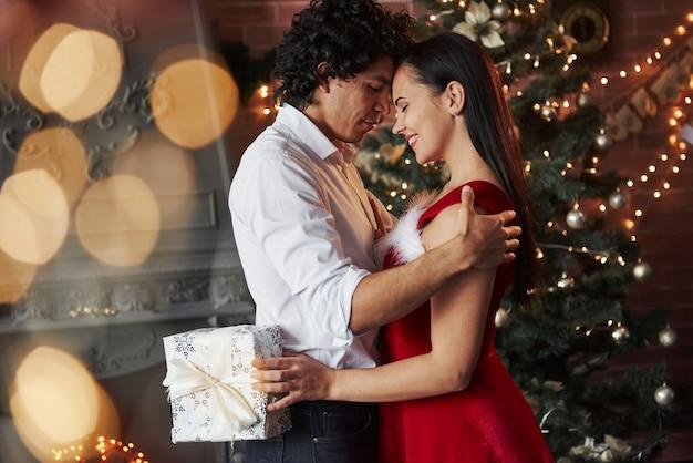 Dziewczyna trzyma białe pudełko. noworoczny wieczór taneczny. urocza wspaniała para spędzająca razem czas.
