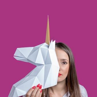 Dziewczyna trzyma biały model 3d papercraft koncepcji unicorn minimal art