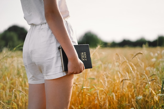 Dziewczyna trzyma biblię w dłoniach. czytanie biblii na polu. koncepcja wiary, duchowości i religii.