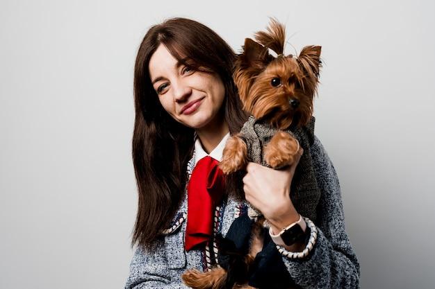 Dziewczyna trzyma brązowego psa na białym tle. młoda atrakcyjna kobieta z uśmiechem psa yorkshire terrier. zamknij zdjęcie. opieki nad zwierzętami. ludzie i zwierzęta.