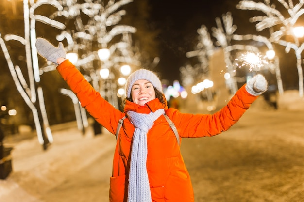 Dziewczyna trzyma brylant w dłoni na zewnątrz zimowego miasta w tle płatki śniegu