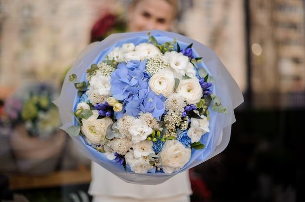 Dziewczyna trzyma bukiet białych róż piwonii i niebieskie hortensje i hiacynt