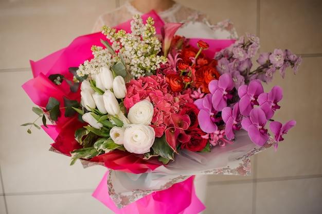 Dziewczyna trzyma bukiet białych tulipanów i bzu, różowe orchidee i hortensje oraz czerwone róże