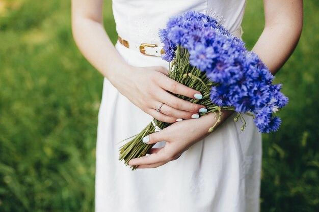 Dziewczyna trzyma bukiet dzikich kwiatów na weselu