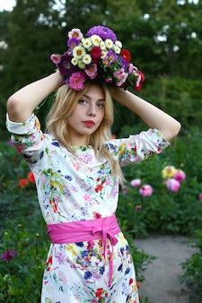 Dziewczyna trzyma bukiet kwiatów na głowie