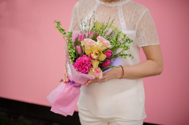 Dziewczyna trzyma bukiet róż, tulipanów, orchidei i hiacyntu