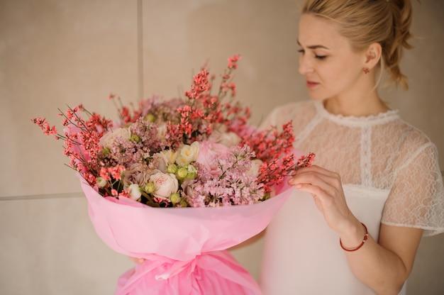 Dziewczyna trzyma bukiet wiosenny delikatny kolor róży i białe kwiaty