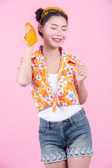 Dziewczyna trzyma butelkę soku pomarańczowego na różowym tle.