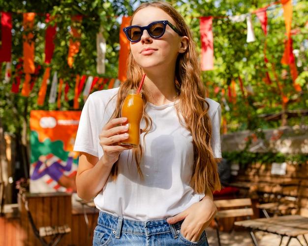 Dziewczyna trzyma butelkę świeżego soku w parku