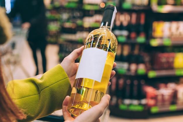 Dziewczyna trzyma butelkę wina w sklepie.