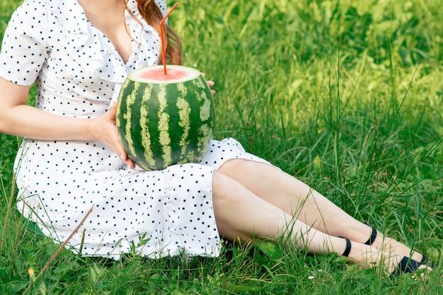 Dziewczyna trzyma całego arbuza z koktajl słomy na tle zielonej trawie.