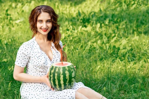 Dziewczyna trzyma całego arbuza z koktajl słomy