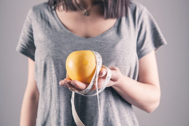 Dziewczyna trzyma centymetr i jabłko w dłoni